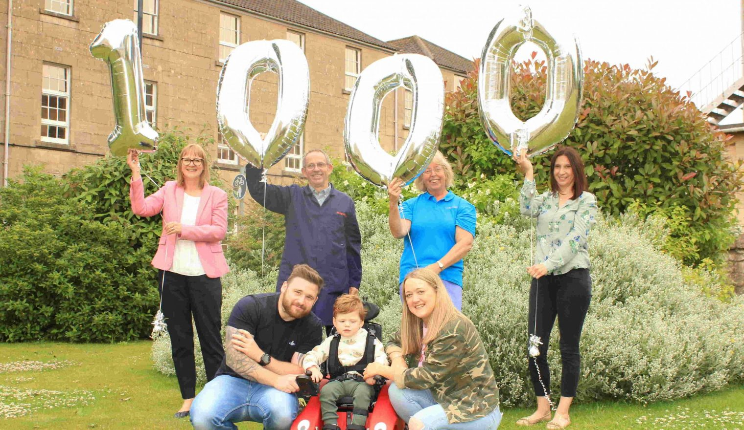 This image shows staff members from Designability along with Parker and his family at the collection of the Wizzybug